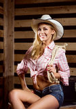 A sexy cowgirl woman posing in a barn Stock Image