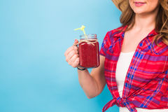 Close up of woman holding fruit juice or cocktail on blue background and copy space Stock Images