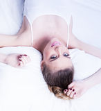 Sexy cute young woman lying on her bed Stock Photos