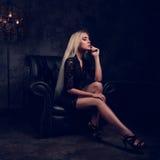 Sexy dünnes blondes Modell, das in Mode Lehnsessel im schwarzen Kleid sitzt Stockbild