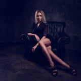 Sexy dünnes blondes Modell, das in Mode Lehnsessel im schwarzen Kleid sitzt Stockfoto