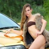 Sexy dame dichtbij de gouden auto Royalty-vrije Stock Foto's