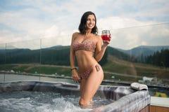 Sexy Dame im Bikini, der draußen mit Cocktail am Jacuzzi im Urlaub gegen Hintergrund der Natur steht Lizenzfreie Stockbilder