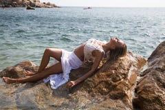 Sexy Dame im nassen weißen Spitzekleid auf felsiger Küste Lizenzfreie Stockfotografie