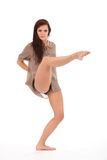 Dancer leg raised toe pointed in pose. Beautiful young female dancer with one leg raised, toe pointed, striking pose on white back ground stock image