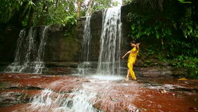 dancer on waterfall in borneo rainforest