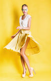Sexy dancing blond woman in yellow skirt Stock Photography