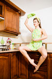 Sexy dancing girl sitting on the table in the kitchen apron hand up looking at copy space on white background portrait Stock Photography