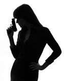 Sexy detective  woman holding aiming  gun silhouette Stock Photo