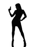 Sexy detective  woman holding aiming  gun silhouette Royalty Free Stock Photography