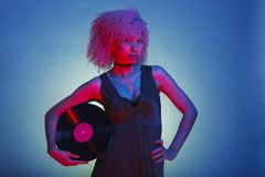 disco woman with afro hair holding a vintage vinyl on neon stock image