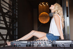 Sexy DJ girl with eyes closed sitting behind the decks Royalty Free Stock Photo