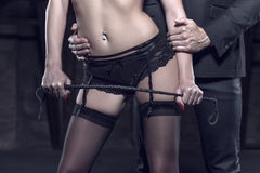 Sexy dominant woman with whip seducing rich man closeup Royalty Free Stock Image