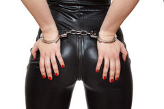 Sexy dominatrix hands on ass in handcuffs closeup isolated Stock Photo