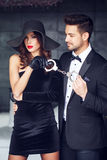 Sexy dominatrix woman holding on handcuffs young macho lover in. Sexy dominatrix women holding on handcuffs young macho lover in tuxedo, bdsm Royalty Free Stock Photo