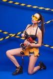 Sexy donkerbruine bouwer op een blauwe achtergrond met een elektrisch gereedschap in de handen van Royalty-vrije Stock Afbeelding