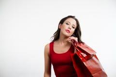 Sexy donkerbruine holding rode het winkelen zakken Royalty-vrije Stock Foto's