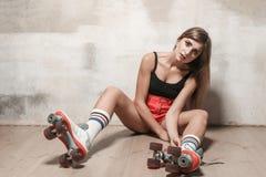 Sexy donkerbruine meisjeszitting op de vloer in rol het schaatsen royalty-vrije stock afbeeldingen