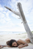 Sexy donkerbruine slaap in zand op strand Royalty-vrije Stock Foto