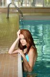 Sexy donkerbruine vrouw die op zwembadrand leunt Stock Foto