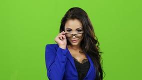 Sexy donkerbruine vrouw met glazen die op camera, het groene scherm stellen