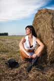 Sexy donkerbruine zitting dichtbij een strobaal Stock Foto's