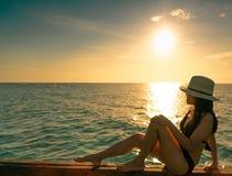 'sexy' e para relaxar a mulher para vestir o biquini preto com chapéu de palha sente-se no feixe de madeira perto da praia da are foto de stock royalty free