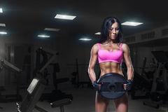 Sexy Eignungsfrau in der Sportabnutzung mit perfektem Eignungskörper in der Turnhalle Stockfotos