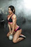 Sexy Eignungsmädchen des Brunette in der Sportabnutzung mit perfektem Körper in der Turnhalle, die vor der Ausbildung des Satzes  Stockbild