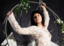 Sexy elegance girl In a lacy peignoir, swinging on a metal swing. holds on metal rods Royalty Free Stock Images