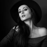 Sexy elegant makeup woman in fashion hat posing on dark shadow b Stock Images