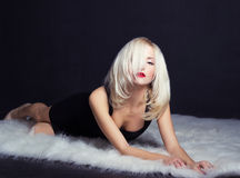 Sexy elegant striking blonde woman with bright makeup red lips in a black dress lies on the white fur in the Studio on a Stock Images