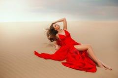 Free Sexy Elegant Stylish Woman Model Lies Posing On Summer Desert. Red Luxury Silk Trendy Long Dress. Beautiful Bare Legs Stock Images - 190455214