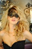 Sexy elegant young lady wearing black corset and Venetian mask. Portrait of beautiful sexy elegant young lady wearing black corset and Venetian mask Stock Photo
