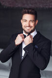 Sexy elegant young macho man tie a bow Royalty Free Stock Photography