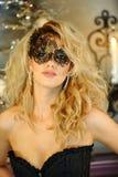 Sexy elegante junge Dame, die schwarzes Korsett und venetianische Maske trägt Stockfoto