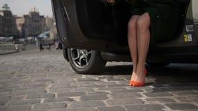 Sexy elegante weibliche Beine, die aus Auto heraus treten