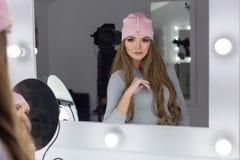 Sexy elegantes Mädchen der schönen Mode mit dem langen Haar, moderne Kappe auf dem Kopf der Abend helles Make-up sitzend und nea  Lizenzfreie Stockbilder