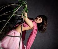 Sexy elegantiemeisje in een roze rok, die op een metaalschommeling slingeren het houden op kettingen royalty-vrije stock foto