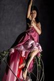 Sexy elegantiemeisje in een roze rok, die op een metaalschommeling slingeren het houden op kettingen stock foto