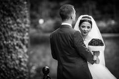 Sexy emotionale Brunettebraut, die Bräutigam umarmt und Blumenstrauß hält Stockbilder