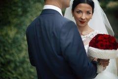 Sexy emotionale Brunettebraut, die Bräutigam umarmt und Blumenstrauß hält Lizenzfreies Stockbild