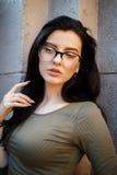 Sexy en mooi brunette in glazen die op de straten stellen royalty-vrije stock foto's