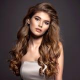 Sexy en schitterende bruin-haired vrouw met lang krullend haar stock fotografie