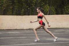 Sexy en sportief meisje die vóór een ras opwarmen Stock Foto's
