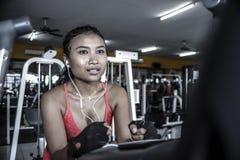 Sexy en zwetende Aziatische vrouw opleiding hard bij gymnastiek die elliptisch pedaling machinetoestel in intense training gebrui royalty-vrije stock fotografie