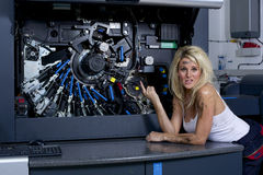 Engineer. A cute looking blonde woman servicing a digital printing press, gets covered in grease and ink royalty free stock image