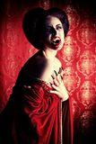 Sexy evil. Portrait of a bloodthirsty female vampire over red vintage background Stock Photos