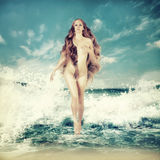 Sexy fairy woman - Aphrodite in sea waves. Sexy fairy slim woman with long curly hair - Aphrodite is in sea water in a spray of sea waves Royalty Free Stock Image