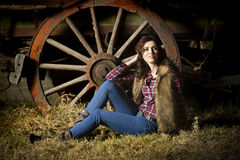 Sexy farm girl posing in front of rustic wagon in barn. Color portrait of a sexy brunette farm girl in casual clothing of jeans, a red checked shirt with fur Stock Photo